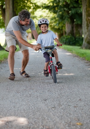 Mid aged man teaching his son to ride a bicycle photo