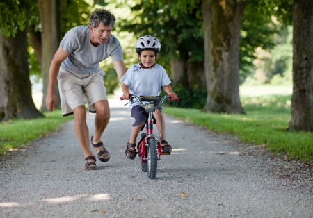 Father teaching his son to ride a bike photo