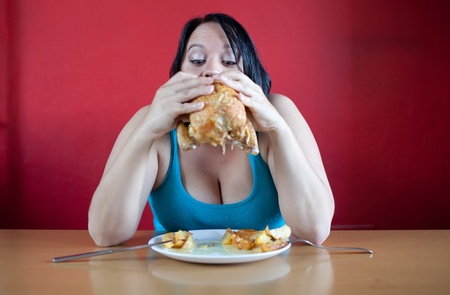 opvulmateriaal: You are what you eat. Overweight woman stuffing herself with chicken.
