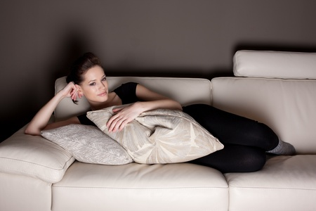 An attractive young woman watching TV, lying on the couch comfortably  photo