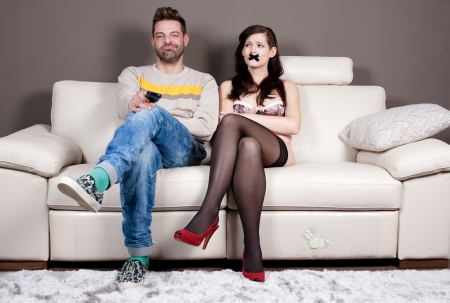 Young woman with taped mouth sitting beside her boyfriendhusband whos enjoying in silence and watching TV.  photo