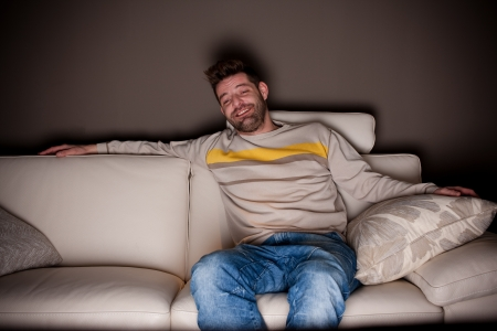 cheesy: A candid photo of a man watching something funny on TV. No fake, cheesy smiles.  Stock Photo