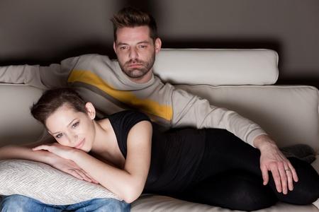 pareja viendo tv: Una foto de una joven pareja viendo TV - no sonr�e un-natural cursi franca  Foto de archivo