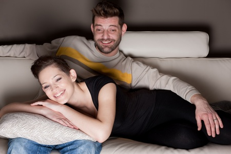 A couple watching TV on a sofa. photo