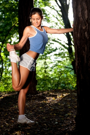 Beautiful young woman stretching in a forrest after jogging Stock Photo - 9912458
