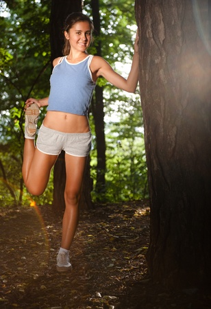 Beautiful young woman stretching in the woods after jogging Stock Photo - 9912457