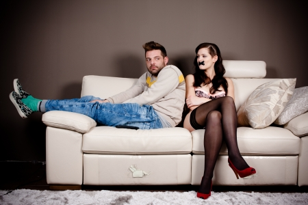 Bizarre living room scene  A woman in lingerie with her mouth taped and a hunched weird man on the couch  High contrast and vignette added  photo