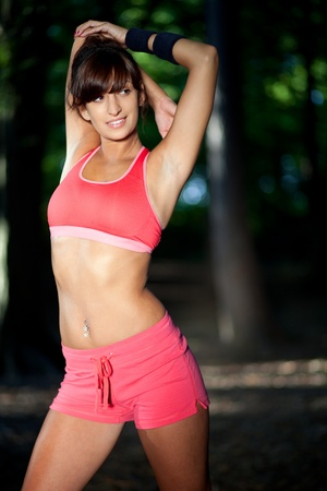triceps: Fit young woman stretching in the woods  Stock Photo
