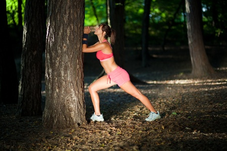 Cute fit young woman stretchingwarming up in a forrest  photo