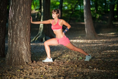 Beautiful young woman stretching/warming up in the forrest photo