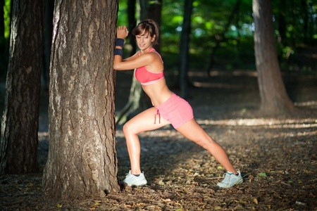 Beautiful young woman stretching/warming up in the woods photo