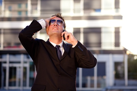 Modern young businessman getting bad news over the phone. Standing in front of an office building. photo
