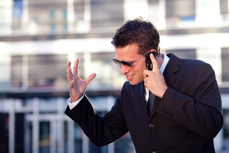 Businessman receiving bad news in front of an office building Stock Photo - 10316499