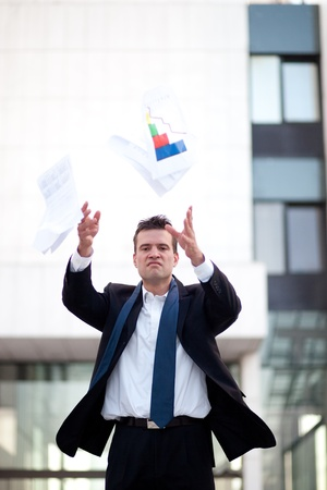 Fired businessman throwing documents in front of an office building Stock Photo - 10316498