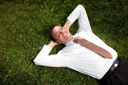 Businessman lying in the grass and relaxing photo