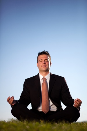 relieve: Businessman meditating outdoors to relieve stress