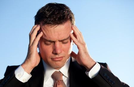 male headache: Empresario bajo estr�s masajeando la cabeza. Dispar� contra el azul del cielo.
