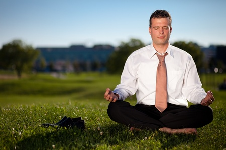 Barefoot businessman meditating in a beautiful park photo