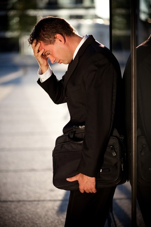 tired businessman: Desperate businessman leaning on an office building