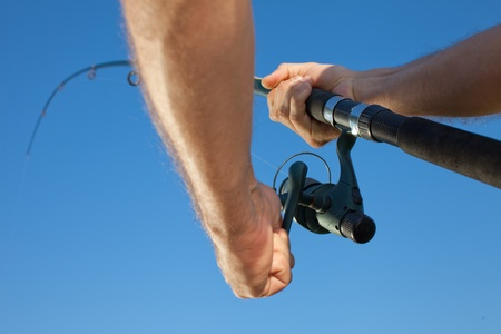 casting: Fisherman reeling in a fish. Shot against clear blue sky.