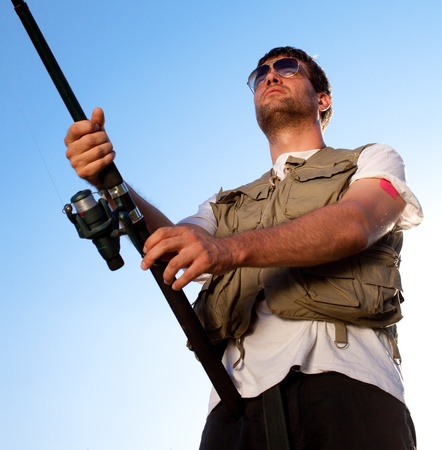 fishing pole: Fisherman against blue sky Stock Photo