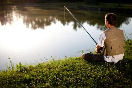 horgász: Ember halászat a tóban. Vissza kilátás. Sekély dof.