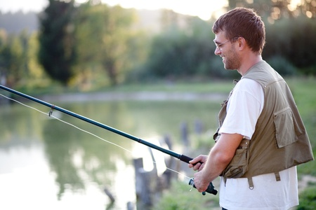 Happy man fishing in a pond. Shallow DOF. photo