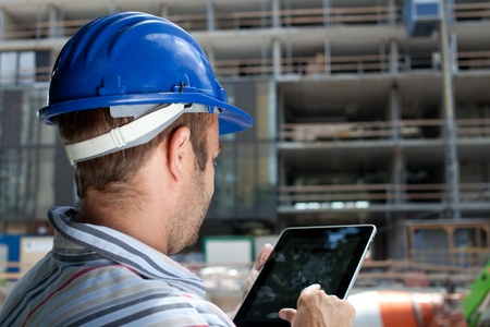 engineer computer: Construction specialist using a tablet computer. At a construction site. Stock Photo