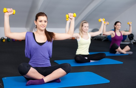 woman lifting weights: A small group of fit young woman lifting weights in a health club