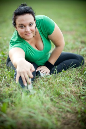 Happy overweight woman stretching in a park. Shallow DOF. Stock Photo - 10475002