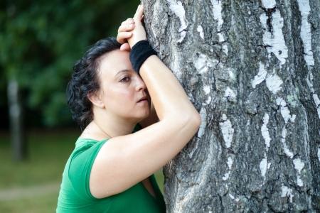 agotado: Mujer agotada sobrepeso apoy�ndose en el �rbol y contuvo la respiraci�n despu�s de haber terminado su formaci�n