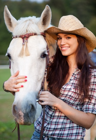 Happy cowgirl with her white horse. Selective focus.