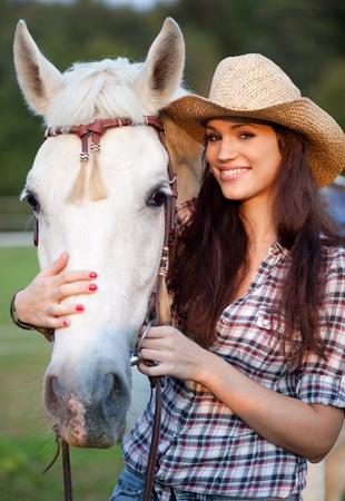 parapente: Vaquera feliz con su caballo blanco. Enfoque selectivo.