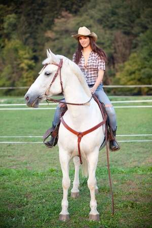 horse riding: Beautiful cowgirl riding a white horse