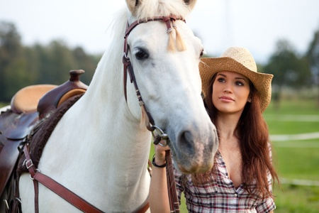 Beautiful cowgirl taking her horse for a ride photo