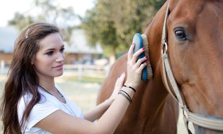 mujer en caballo: Atractiva joven rozando un caballo. Enfoque selectivo.