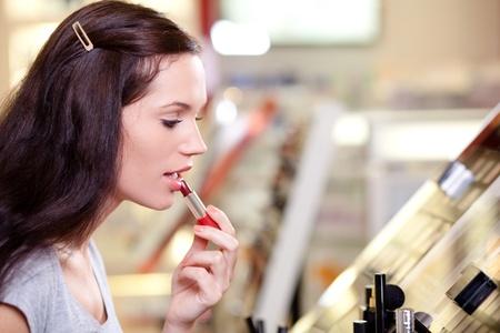 Beautiful young woman buying lipstick. Shallow DOF. photo