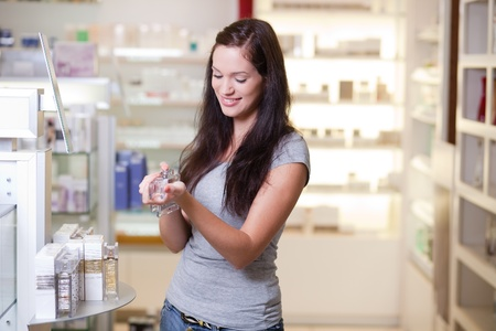 Happy young woman buying a perfume. Shallow DOF. photo
