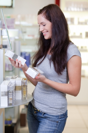 mart: Attractive happy young woman buying perfume. Shallow DOF. Stock Photo