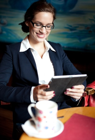 Young businesswoman using her tablet computer on a coffee break. Selective focus photo