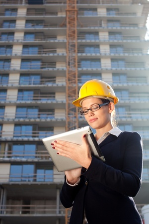 Beautiful young construction engineerarchitect using tablet computer at construction site photo