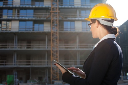 Female construction engineerarchitect using tablet computer at construction site photo