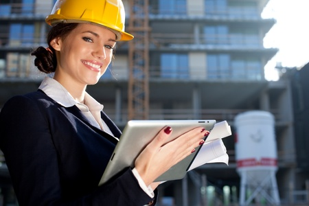 Attractive happy female construction engineerarchitect with a tablet computer at a construction site photo