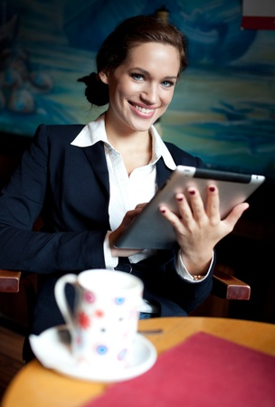 Beautiful businesswoman using tablet computer on coffee break. Selective focus. photo