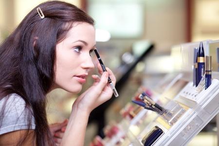 eyeliner: Young woman testing cosmetics. Selective focus.