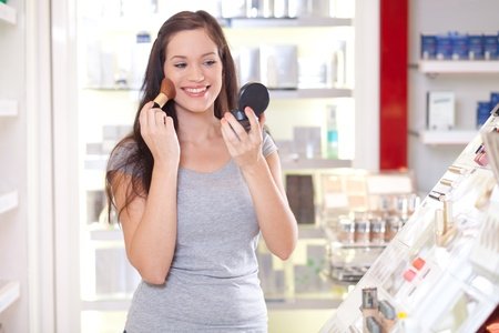 Beautiful young woman testing make up in a drug store photo