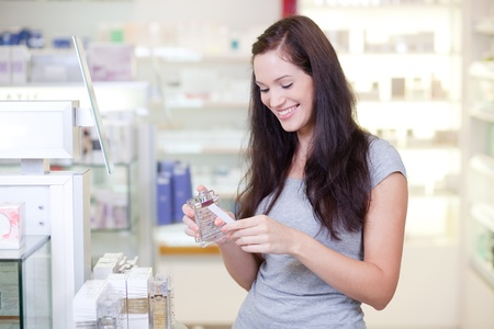 cosmetic products: Beautiful young woman buying perfume. Selective focus. Stock Photo