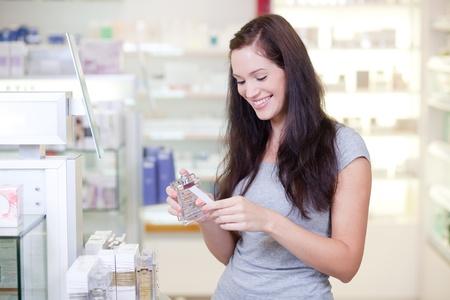 productos de belleza: Joven y bella mujer comprar perfume. Enfoque selectivo.