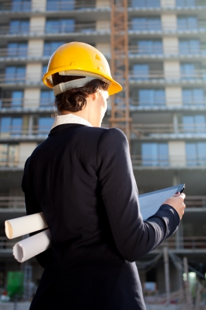 Female architect construction engineer reviewing plans at construction site photo