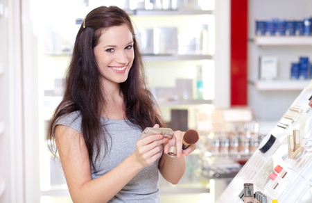 Beautiful young woman testing powder. Shopping for cosmetics. photo